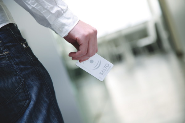 A man approaching a door with a salto access card.