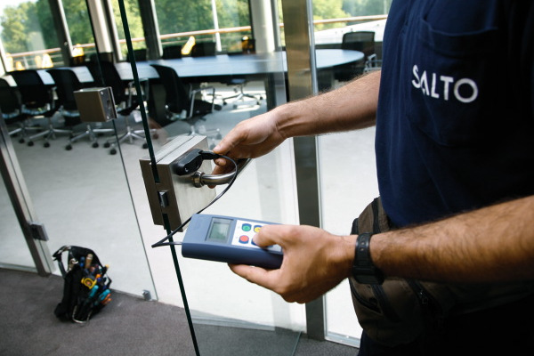 Salto engineer testing a lock on a conference room glass door.