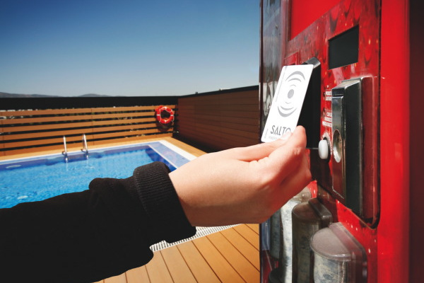 Salto access card being used on a vending machine by a swimming pool.